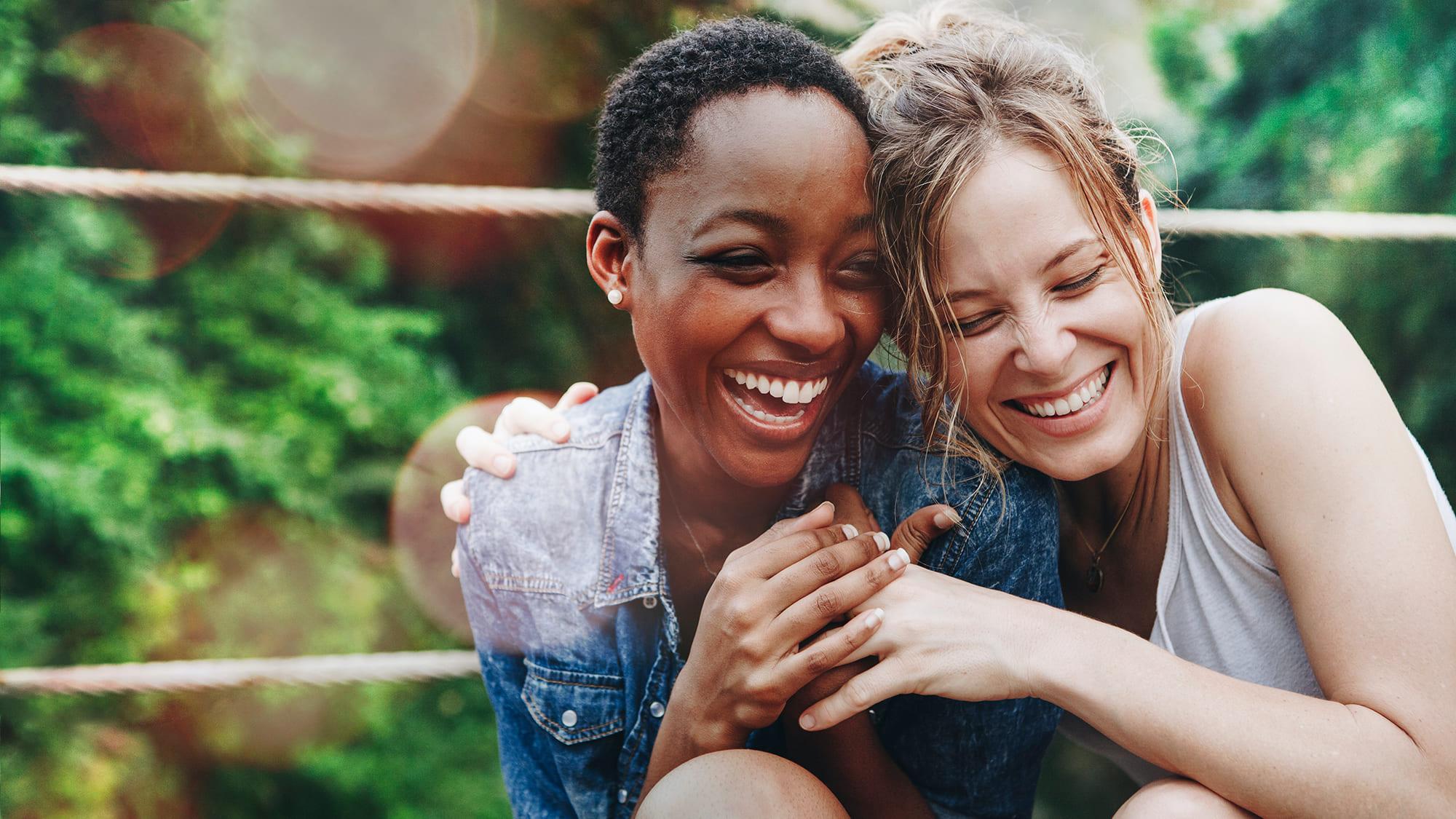 zwei Frauen unterschiedlicher Herkunft liegen sich lachend in den Armen