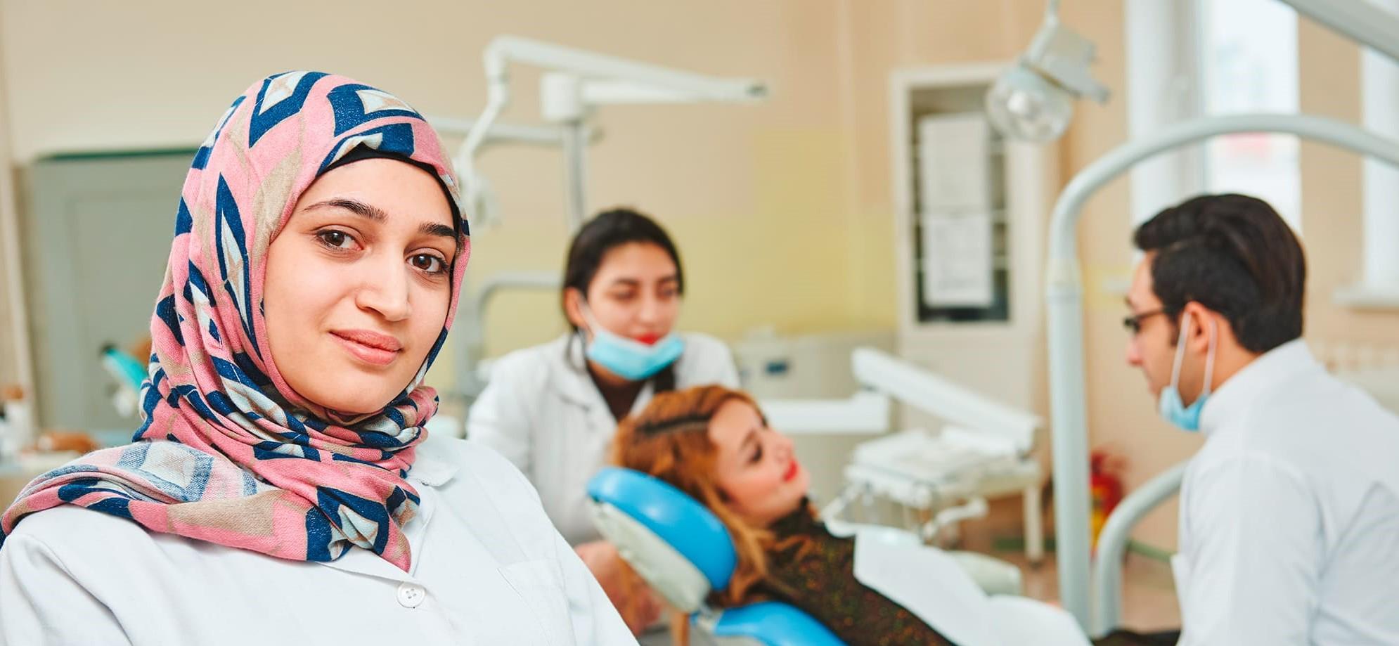 Frau mit Kopftuch im Arztkittel im Vordergrund - im Hintergrund Patientin auf Zahnarztstuhl