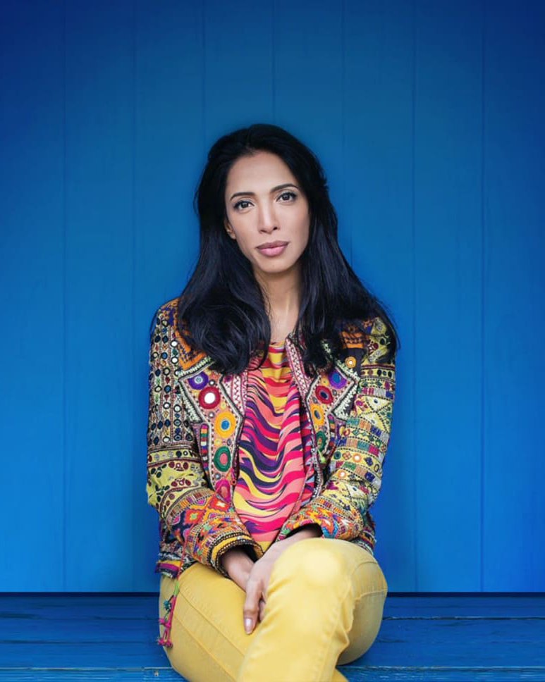 Zohre Esmaeli Frau mit schwarzen Haaren sitzend in bunt gemusterter Jacke und gelber Hose vor blauem Hintergrund