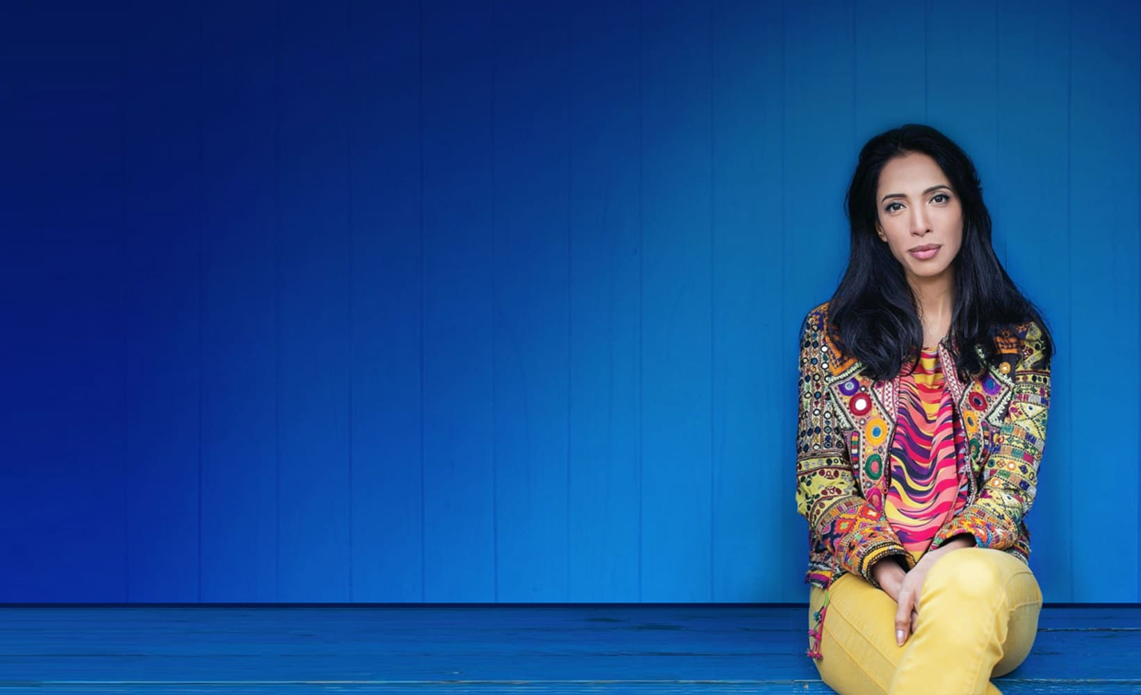 Zohre Esmaeli woman with black hair sitting in a colorful patterned jacket and yellow pants in front of a blue background